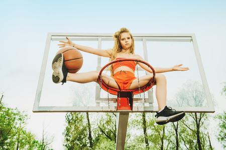 Un portrait en pied d'une adolescente sportive posant sur la pincée de basket-ball. Mode sportive, mode de vie actif, basket-ball. Banque d'images
