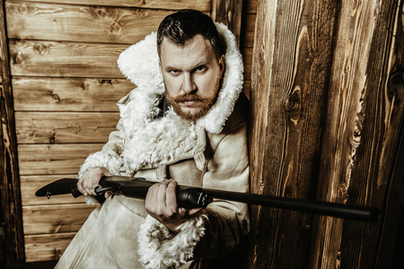 A portrait of a hunter man standing at the wooden house. Man, hunting, musket. Stock Photo