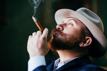 Ein Nahaufnahmeporträt eines nachdenklichen Mannes mit einer Zigarre, die im Studio über dem schwarzen Hintergrund posiert. Männer Schönheit, Mode, Stil.