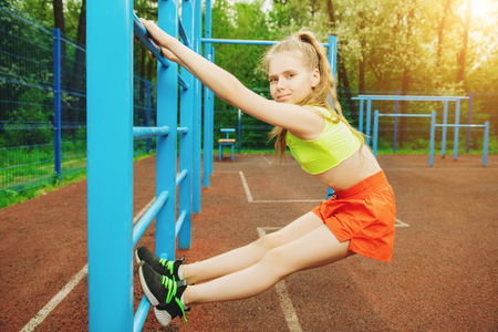 Ein Porträt in voller Länge eines sportlichen Teenager-Mädchens, das auf dem Sportplatz posiert. Sportmode, aktiver Lebensstil. Standard-Bild