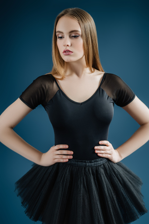 A portrait of a young pretty woman posing in the studio over the blue background. Fashion for ballet dancers, beauty.