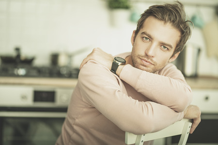 A portrait of a handsome man in a pink sweater. Beauty, fashion for men.