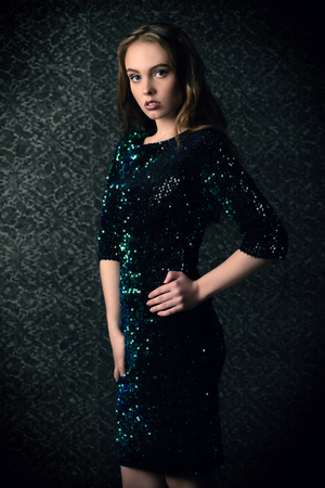 A portrait of a young fashionable woman posing in the studio over the dark background. Evening women fashion, beauty.