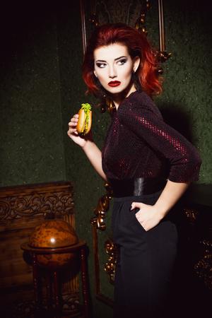 Ein Porträt einer schönen Frau, die im Vintage-Interieur posiert und eine Mahlzeit zu sich nimmt. Schönheit, Mode, Interieur.