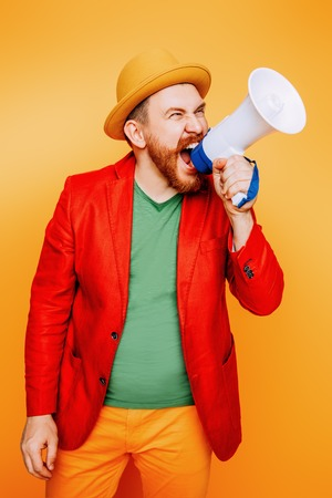 A portrait of a bright man posing in the studio with a mouthpiece over the yellow background. Men, beauty, colors, fashion.