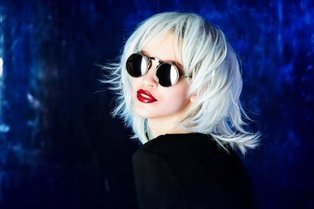 Portrait de gros plan d'une belle femme blonde à lunettes de soleil élégantes sur fond sombre. Beauté, concept de mode. Maquillage et cosmétiques. Tourné en studio.