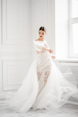 Ein Porträt in voller Länge einer charmanten Dame in einem Hochzeitskleid, die drinnen posiert. Hochzeitsmode, Braut.