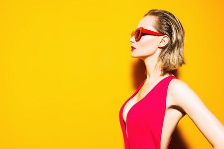 A portrait of a bright girl wearing a swimsuit and posing over the yellow background. Summer fashion, beauty.
