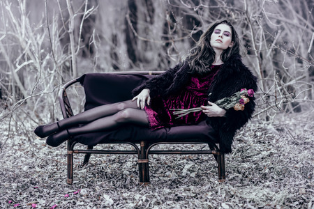 A portrait of a beautiful mysterious girl in black posing on the armchair in the forest. Beauty, fashion, nature.