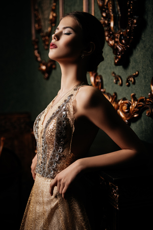 A portrait of a mysterious lady in a beige dress posing indoor. Fairy tale, beauty, fashion. Imagens