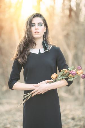 Een portret van een mooi mysterieus meisje in het zwart poseren met bloemen in het bos. Schoonheid, mode, natuur.