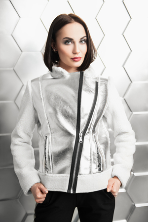 A portrait of a beautiful woman wearing a white and silver coat. Fashion, style.