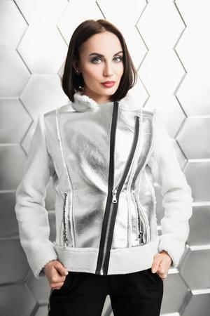 Un retrato de una bella mujer con un abrigo blanco y plateado. Estilo de moda.
