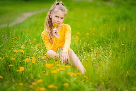 Ein Porträt eines fröhlichen Teenager-Mädchens, das auf dem Gebiet posiert. Kinder, Natur, sommerliche Freizeitmode, positiv. Standard-Bild