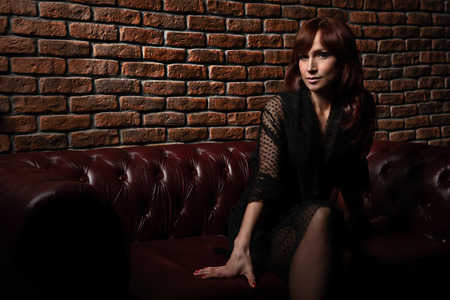 A portrait of a femme fatale in dark clothes posing on a leather sofa on a brick wall background.