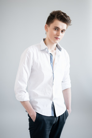 A portrait of a young guy in a shirt posing indoor. Fashion and beauty for men.