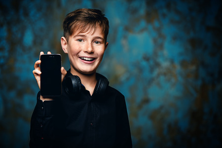 A portrait of a young boy with a smartphone and headphones. Fashion, gadgets. 스톡 콘텐츠
