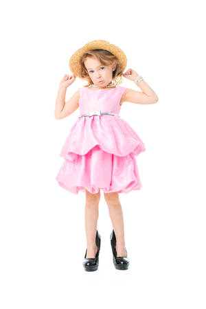 A full length portrait of a pretty girl in a pink dress and high-heeled shoes posing in the studio over the white background. Kids, fashion, beauty. Banco de Imagens