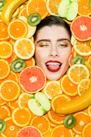 A portrait of a bright beautiful girl with juicy fruit posing in the studio over the yellow background. Beauty, health. 写真素材 - 124620788