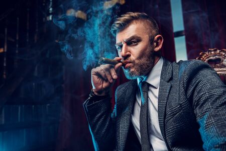 A portrait of a handsome mature man in a formal costume smoking a cigar in the interior. Mens beauty, fashion. Imagens