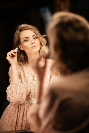 A portrait of a beautiful girl posing while doing make up. Beauty, make up. Banco de Imagens