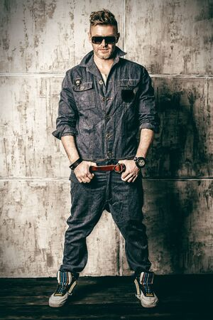 A full length portrait of a handsome brutal mature man posing in the studio over the grey wall. Casual denim fashion for men.