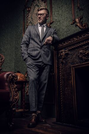 A full length portrait of a handsome mature smiling man in a formal costume smoking a cigar in the classic interior. Mens beauty, fashion.