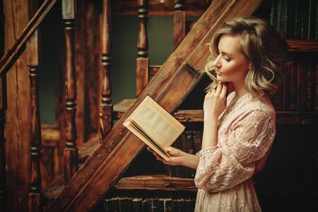 A full length portrait of a beautiful woman posing in the interior reading a book. Interior, fashion. Reklamní fotografie