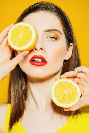 A portrait of a bright beautiful girl with a juicy orange posing in the studio over the yellow background. Beauty, health.