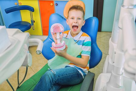 A portrait of a child boy in the cabinet of a dentist. treatment, medicine, hospital. Reklamní fotografie