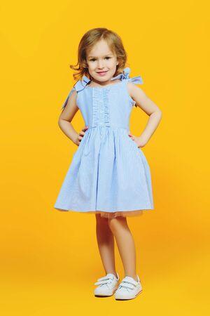 Un ritratto a figura intera di una bella ragazza in un abito blu in posa in studio su sfondo giallo. Bambini, moda, bellezza. Archivio Fotografico