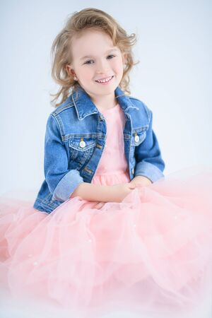 A portrait of a pretty girl in a pink dress and a denim jacket posing in the studio over the white background. Kids, fashion, beauty.