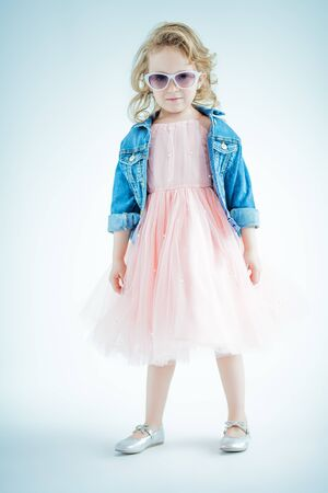 A full length portrait of a pretty girl in a pink dress and a denim jacket posing in the studio over the white background. Kids, fashion, beauty, optics Reklamní fotografie