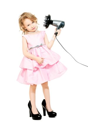 A full length portrait of a pretty girl in a pink dress and high-heeled shoes posing in the studio over the white background with a hairdryer. Kids, fashion, beauty. Reklamní fotografie