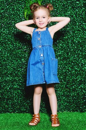 A full length portrait of a pretty girl in a denim sundress posing over the green background. Kids, fashion, beauty.