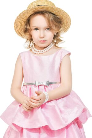 A portrait of a pretty girl in a pink dress posing in the studio over the white background. Kids, fashion, beauty. Reklamní fotografie