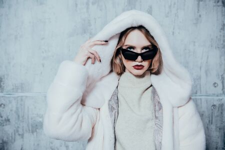 A portrait of a beautiful woman wearing a white fur coat with hood and sunglasses. Beauty, winter fashion, style.