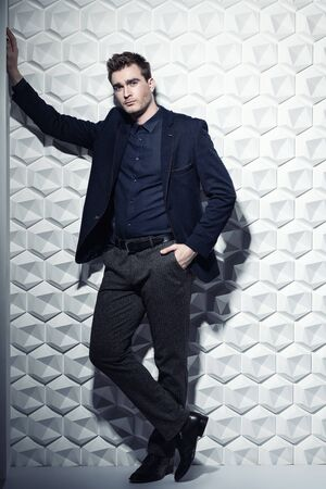 A full length portrait of a fashionable young man wearing formal classic clothes posing in the studio. Fashion for men.