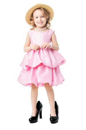 A full length portrait of a pretty girl in a pink dress and high-heeled shoes posing in the studio over the white background. Kids, fashion, beauty. Reklamní fotografie