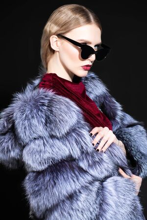 A portrait of a beautiful woman wearing a fur coat with hood and sunglasses. Beauty, winter fashion, style.