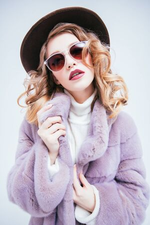 A portrait of a beautiful woman wearing a fur coat and a hat and sunglasses. Beauty, winter fashion, style.