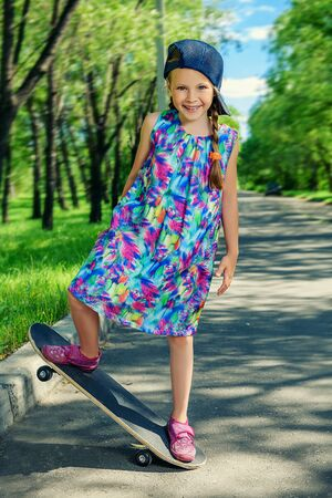 Cheerful little girl riding on a skateboard in the park. Outdoor activity. Summer holidays.