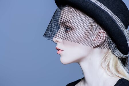 Fashion shot of a stunning young woman in hat with a veil. Headwear style.