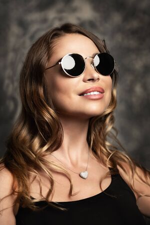 Amazing woman wearing elegant fitting dress and sunglasses. Beauty, fashion concept. Evening dresses collection. Reklamní fotografie