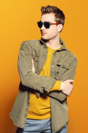 A portrait of a fashionable young man posing in the studio over the yellow background. Casual fashion for men. Reklamní fotografie