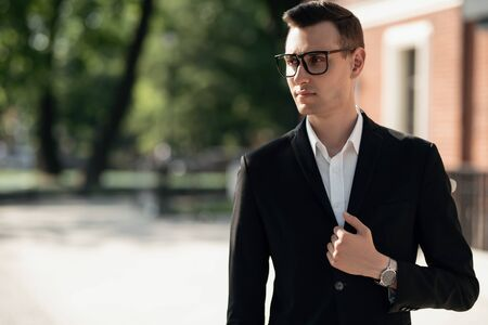 A portrait of a goodlooking young guy walking in the street. Mens beauty, fashion. Reklamní fotografie