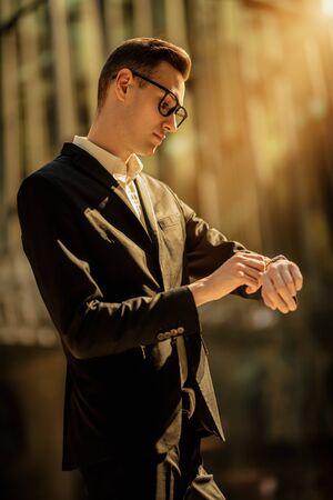 Een portret van een knappe jonge kerel die op straat loopt. Mannen schoonheid, mode. Stockfoto