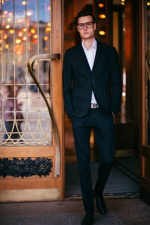 A full length portrait of a goodlooking young guy walking in the street. Formal men fashion.