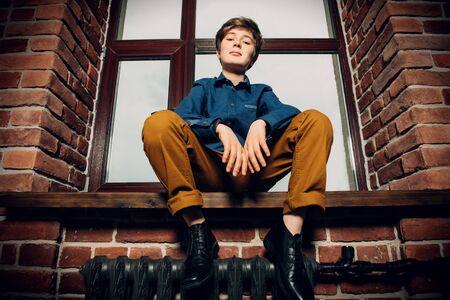A full length portrait of a young boy posing near the window. Kids, fashion, freedom feeling.