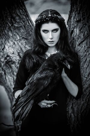 A portrait of a beautiful mysterious girl in black posing in the forest with a raven. Beauty, fashion, nature. Archivio Fotografico